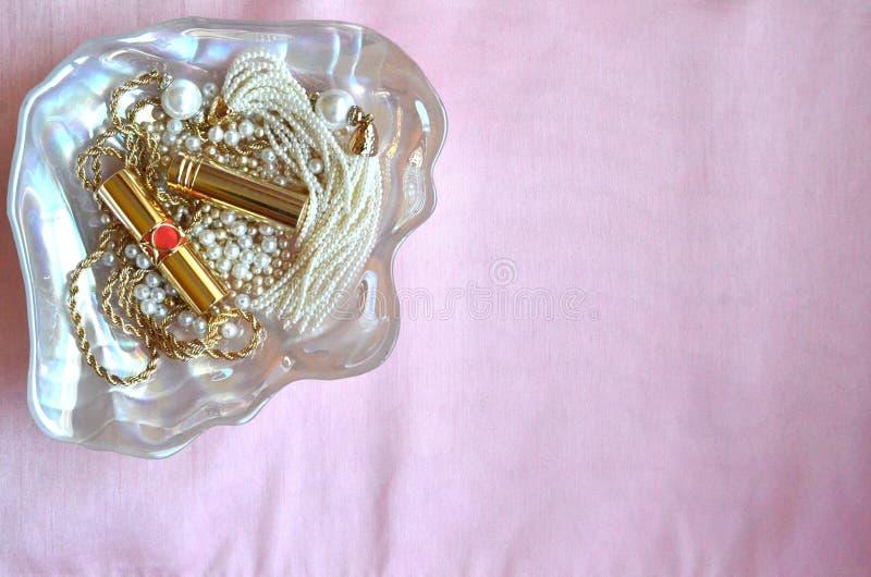 Perlmuttoberteilschüssel mit Perlen, Lippenstiften und Goldschmuck auf rosa silk Hintergrund mit Kopienraum lizenzfreie stockfotografie