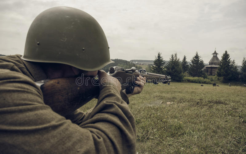 PERM, RUSSIA - JULY 30, 2016: Historical reenactment of World War II, summer, 1942. Soviet soldier aiming a rifle.  royalty free stock photography