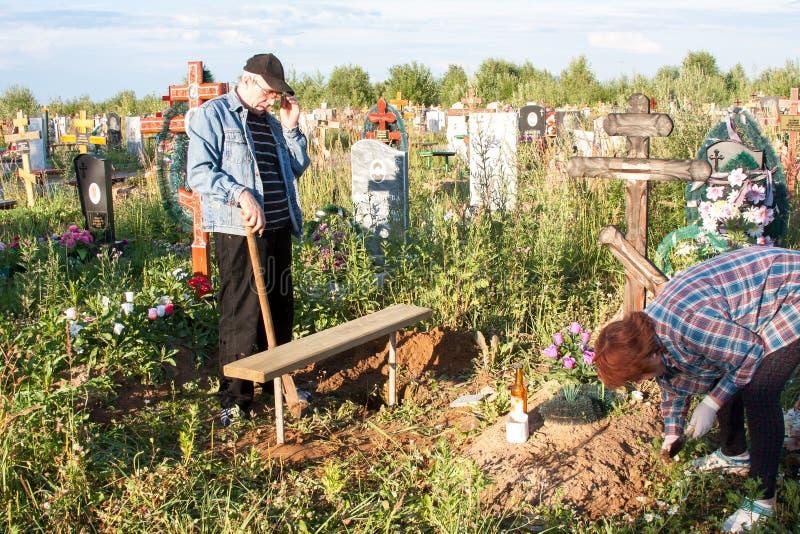 Perm, Russia - 13 luglio 2016: L'uomo e la cura della donna di una tomba fotografia stock