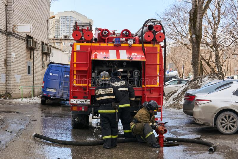 Firefighters of the Ministry for Emergency Situations of the Russian Federation use a fire hydrant next to the fire truck. Perm, Russia - March 20, 2020 stock photos