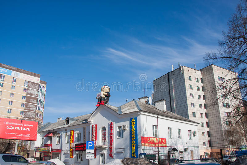 Perm, Russia - March 31.2016: Toy inflatable man on the roof of. The car shop building stock photography