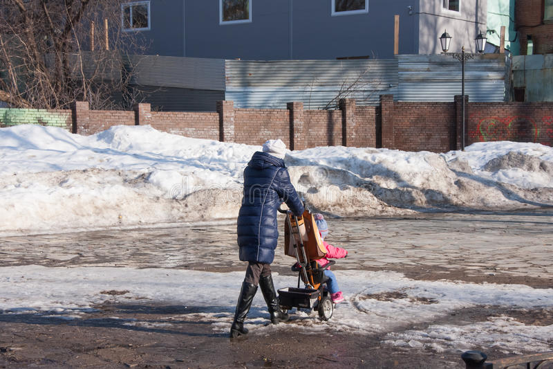 Perm, Russia - March 31.2016: Woman with a stroller on a walk in. Perm, Russia - March 31.2016: Woman with a pram for a walk in the park in spring sunny day royalty free stock photos