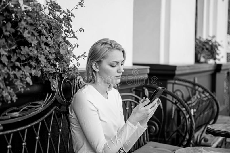 Permaneça em contacto Fundo urbano texting do terraço do café do smartphone da cara calma da mulher O branco texting do amigo da  imagem de stock royalty free