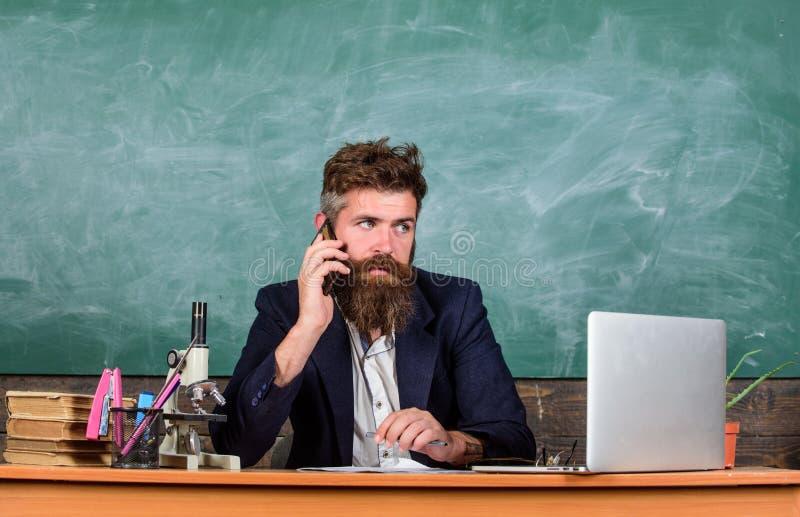 Permaneça em contacto Telefone celular da chamada do professor quando sente o fundo do quadro da sala de aula Conversa farpada do fotos de stock royalty free