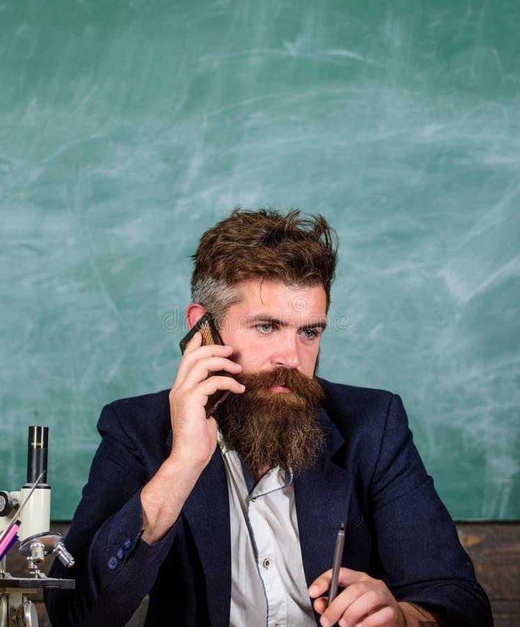 Permaneça em contacto Telefone celular da chamada do professor quando sente o fundo do quadro da sala de aula O pedagogo permanec imagens de stock royalty free