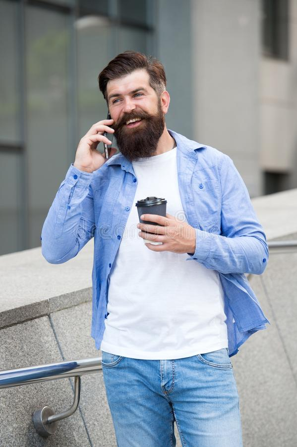 Permane?a em contacto Caminhada farpada do homem com fundo urbano do copo do smartphone e de café Smartphone de sorriso da cara d fotos de stock