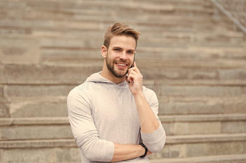 Permane?a em contacto Equipe caminhadas farpadas com smartphone, fundo urbano com escadas A cara de sorriso agrad?vel do homem fa imagens de stock