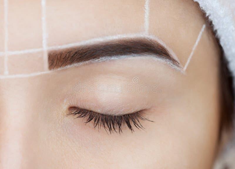 Permanent maak wenkbrauwen van mooie vrouw met dikke brows goed stock afbeeldingen