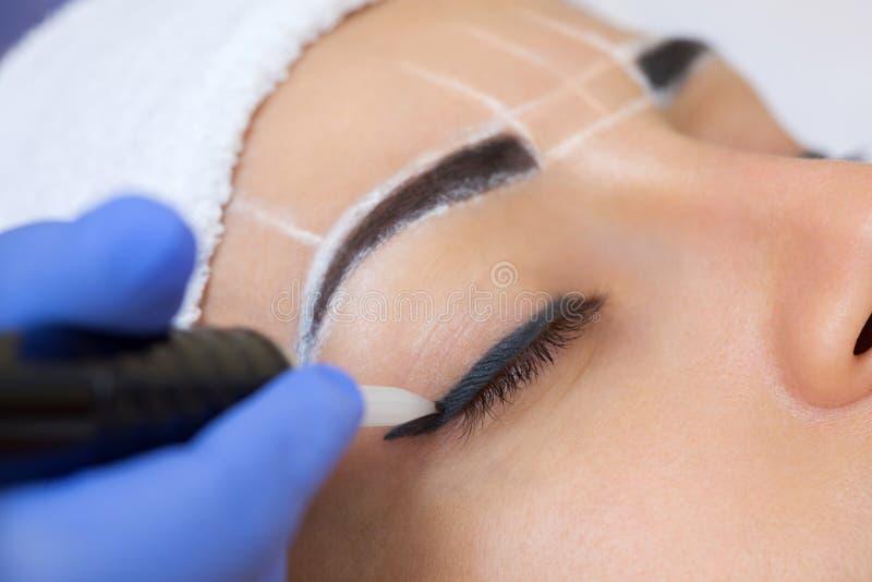 Permanent maak wenkbrauwen van mooie vrouw met dikke brows in schoonheidssalon goed stock fotografie