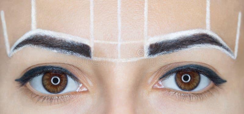 Permanent maak wenkbrauwen van mooie vrouw met dikke brows in schoonheidssalon goed royalty-vrije stock afbeeldingen