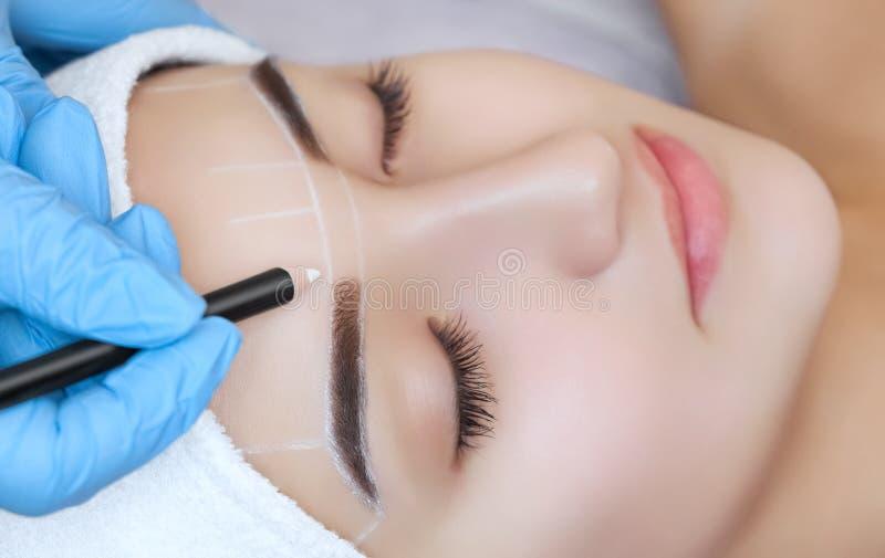 Permanent maak wenkbrauwen van mooie vrouw met dikke brows in schoonheidssalon goed stock afbeelding