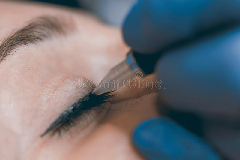 Permanent make up. Cosmetologist applying permanent makeup on eyes. stock photography