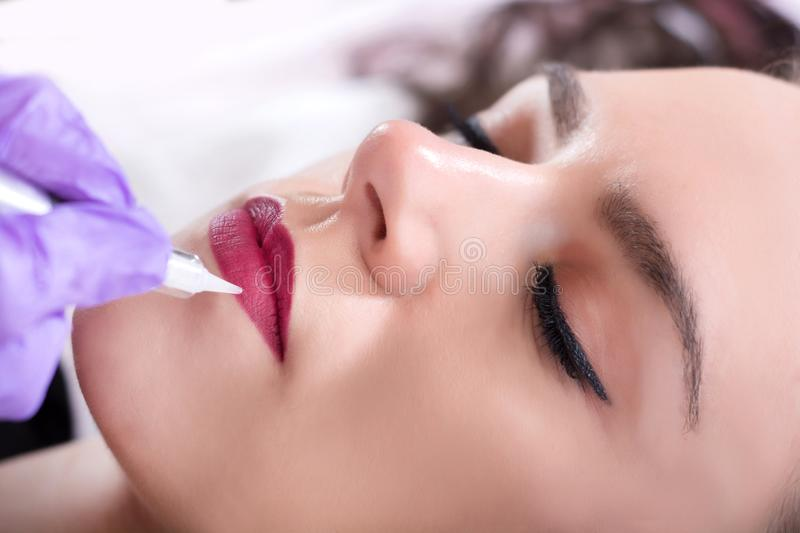 Permanent make up for red lips of beautiful woman in beauty salon royalty free stock images