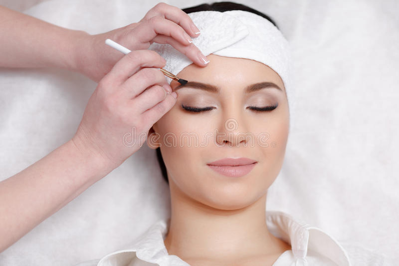 Permanent make-up wizard makes eyebrow correction procedure stock images