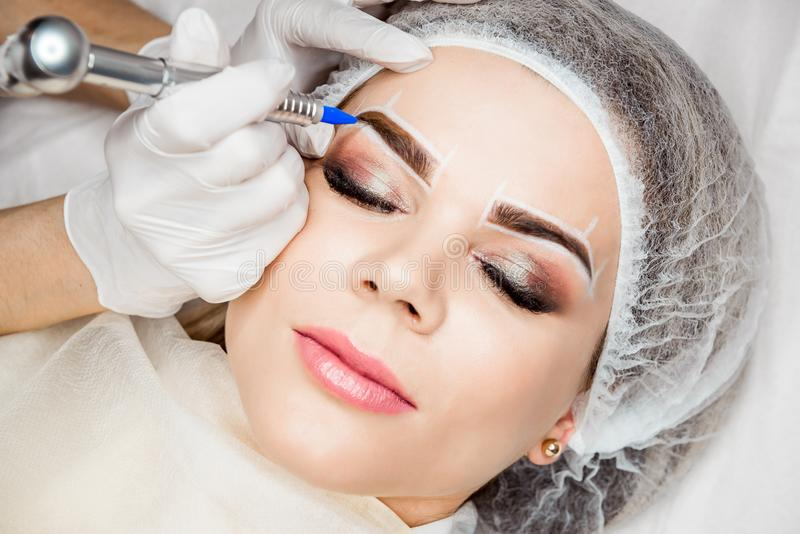 Permanent Makeup For Eyebrows. Closeup Of Beautiful Woman With Thick Brows In Beauty Salon. Beautician Doing Eyebrow stock photo