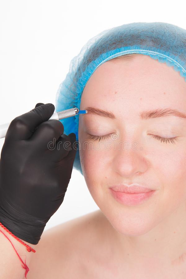 Permanent Makeup For Eyebrows. Microblading brow. Beautician Doing Eyebrow Tattooing For Female Face. Beautiful young. Girl in a beauty salon stock photo
