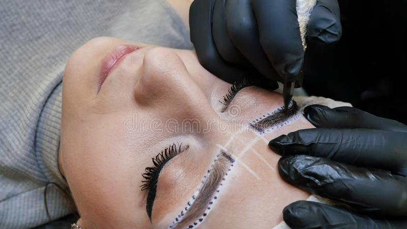 Permanent makeup. Permanent tattooing of eyebrows. Cosmetologist applying permanent make up on eyebrows- eyebrow tattoo. stock images