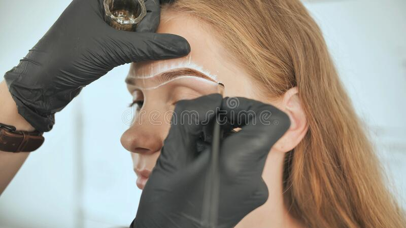 Permanent makeup. Permanent tattooing of eyebrows. Cosmetologist applying permanent make up on eyebrows - eyebrow tattoo royalty free stock photography