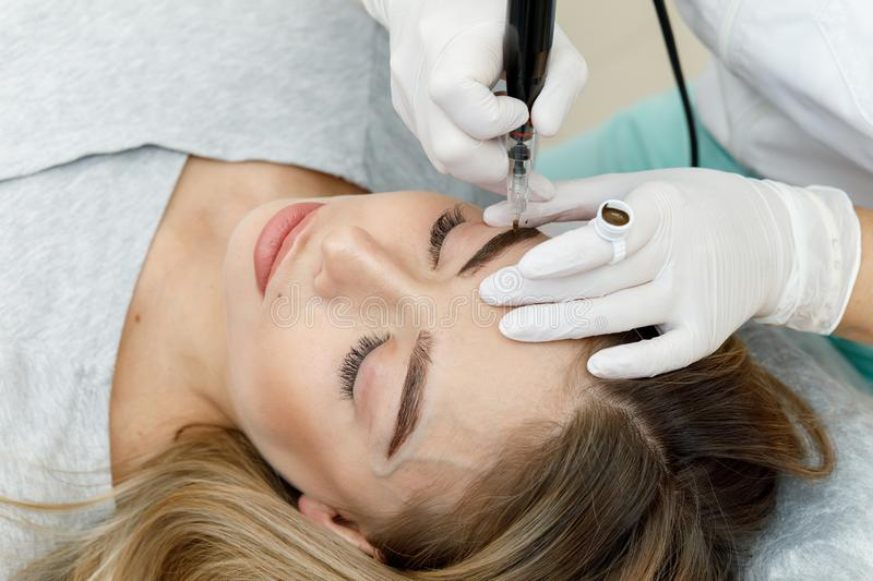 Permanent makeup, tattooing of eyebrows. Cosmetologist applying make up royalty free stock images
