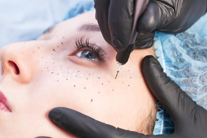 Microblading tattooing freckles to a woman in a beauty salon royalty free stock images