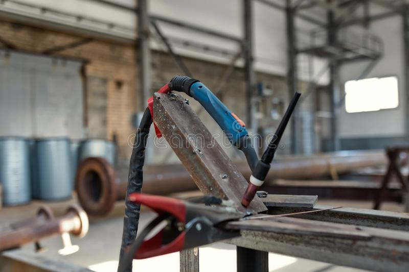 Permanent place of welding argon-arc weld. Ing in a small industrial shop. Equipment, burner and accessories for welding stock images