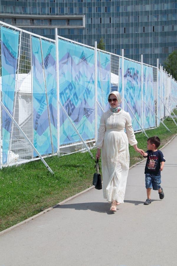 PERMANENT RYSSLAND - JUNI 13, 2013: Kvinna med sonen arkivfoto