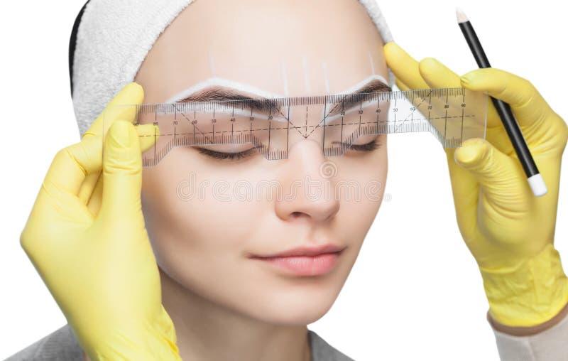 Permanent smink för ögonbryn av den härliga kvinnan med tjocka krön i skönhetsalong royaltyfri foto