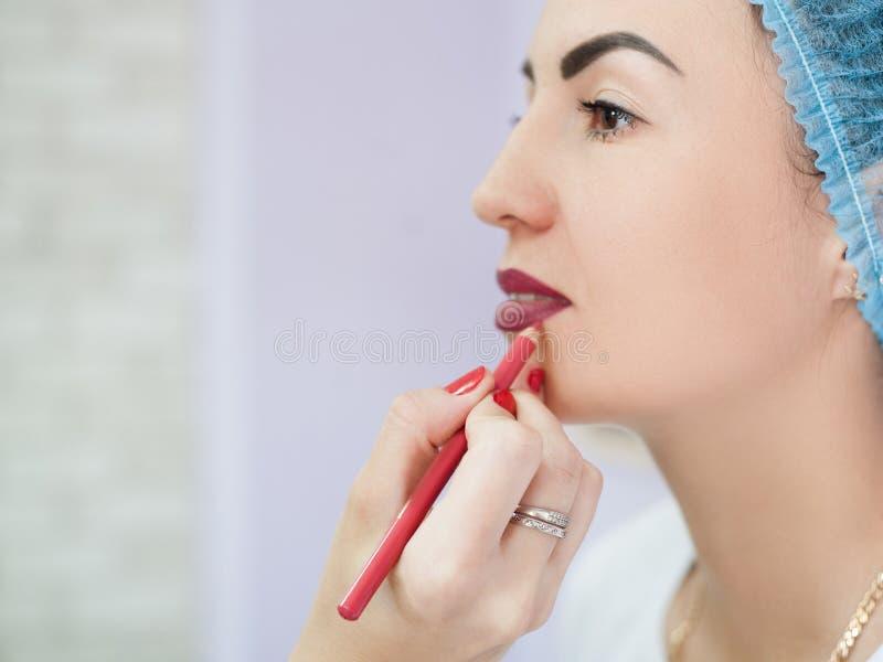 Permanente make-up bogundy pencil contour lippen royalty-vrije stock afbeeldingen