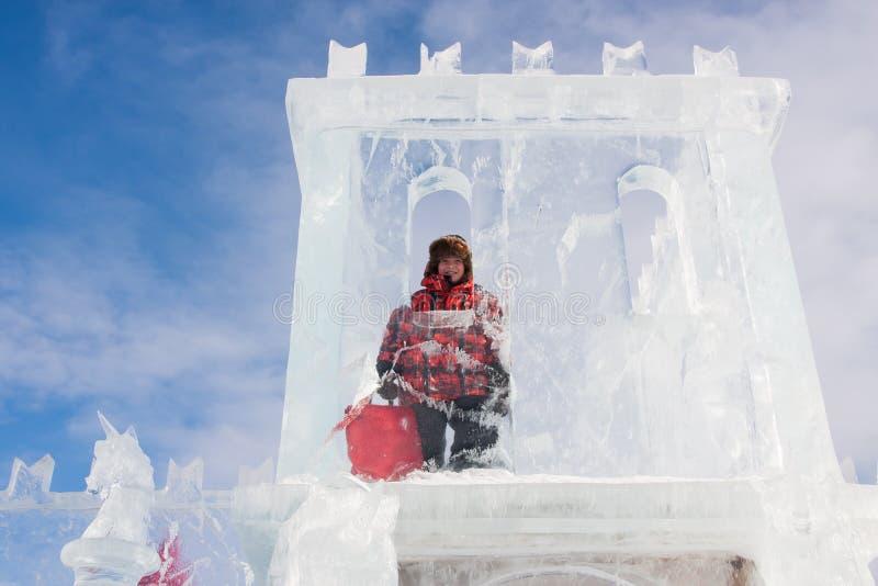 PERMANENTE, RÚSSIA fevereiro, 06 2016: Menino com uma escultura de gelo foto de stock royalty free