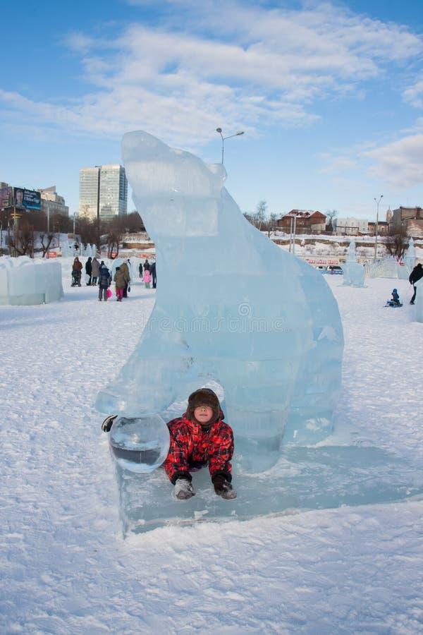 PERMANENTE, RÚSSIA, fevereiro, 06 2016: O menino em uma escultura de gelo do urso fotos de stock