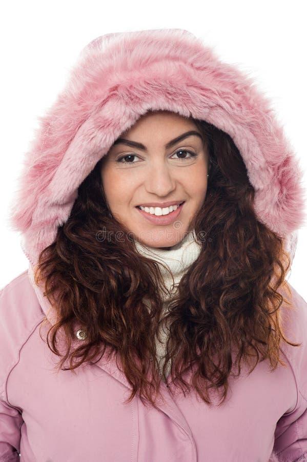 Permed Haarfrau, die rosa Haubenwinterjacke trägt lizenzfreies stockfoto