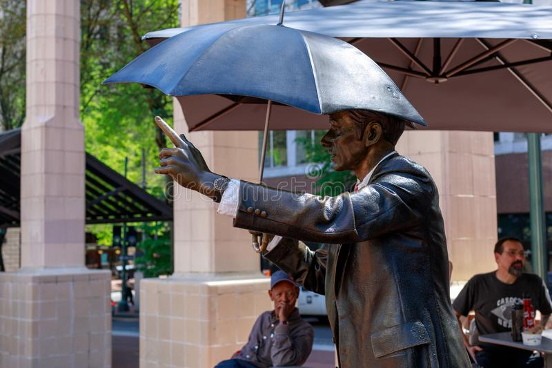 Permettez-moi, également connu comme homme de parapluie, êtes une sculpture en bronze iconique dans la place de tribunal de pionn images stock