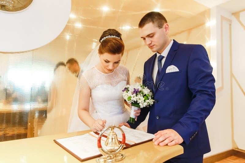 Permis de mariage de signature de jeunes mariés photo stock