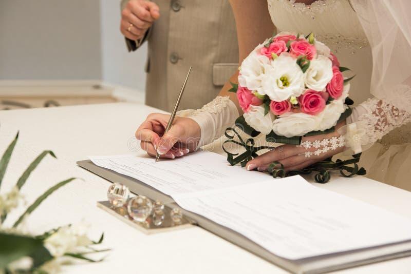 Permiso de matrimonio de firma de la novia o contrato que se casa fotos de archivo libres de regalías