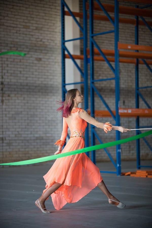 Permomer del circo della giovane donna che balla con il nastro relativo alla ginnastica in mani dell'interno immagine stock
