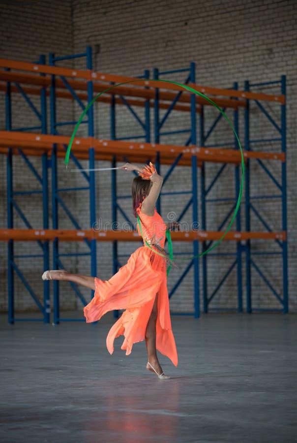 Permomer del circo della giovane donna che balla con il nastro relativo alla ginnastica in mani nel magazzino immagini stock
