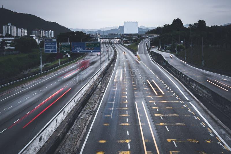 Permuta occupata della gente con le automobili facendo uso della strada principale fra le città immagini stock