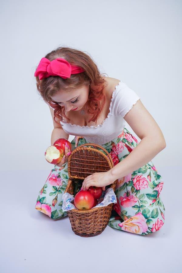 Perno bonito encima de la presentación feliz de la chica joven caucásica con las manzanas rojas señora linda del vintage en el ve fotos de archivo