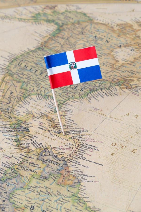 Perno de la bandera de la República Dominicana en un mapa del mundo foto de archivo