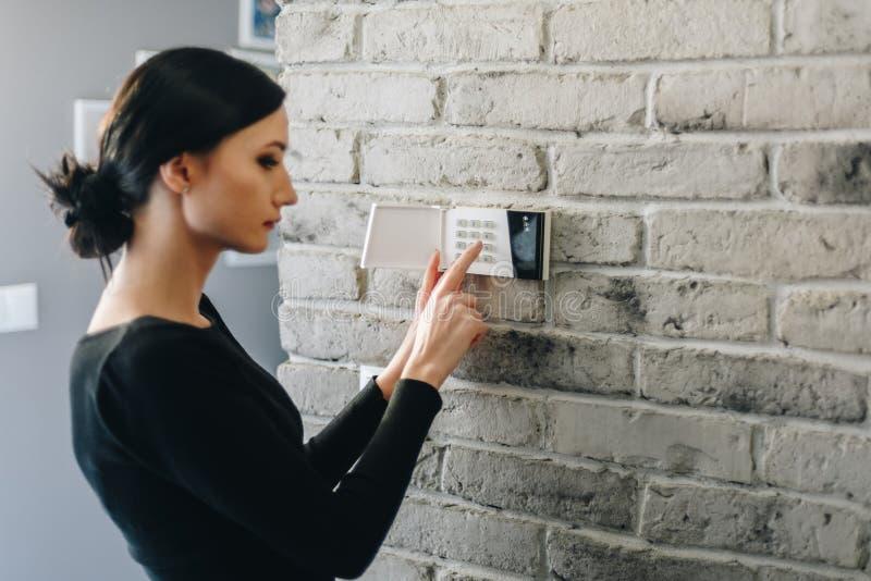 Perno de la seguridad de la mujer que entra joven en el telclado numérico casero de la alarma imágenes de archivo libres de regalías