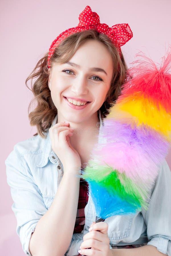 Perno de limpieza encima de la mujer La muchacha modela sonriente sostiene el cepillo colorido del plumero servicio de la limpiez fotografía de archivo