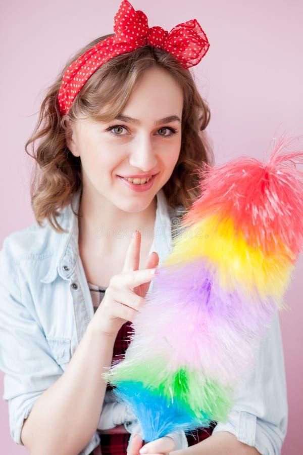 Perno de limpieza encima de la mujer La muchacha modela sonriente sostiene el cepillo colorido del plumero servicio de la limpiez imagen de archivo libre de regalías