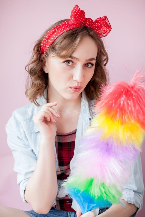 Perno de limpieza encima de la mujer La muchacha modela sonriente sostiene el cepillo colorido del plumero servicio de la limpiez imagenes de archivo