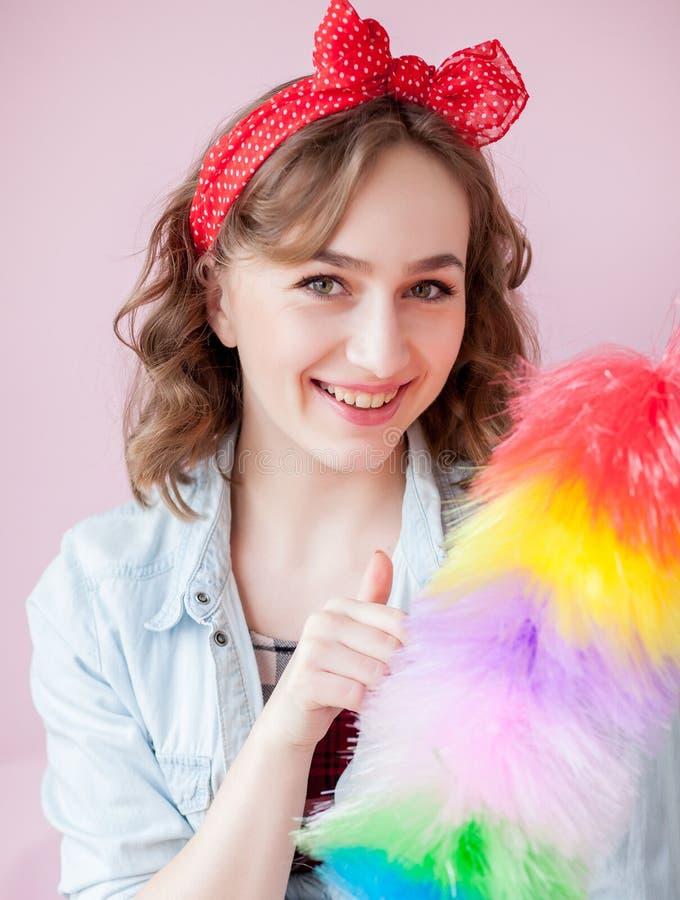 Perno de limpieza encima de la mujer La muchacha modela sonriente sostiene el cepillo colorido del plumero servicio de la limpiez imágenes de archivo libres de regalías