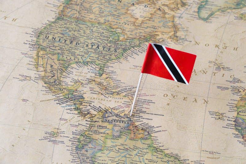 Perno della bandiera di Trinidad e Tobago su una mappa di mondo fotografia stock libera da diritti