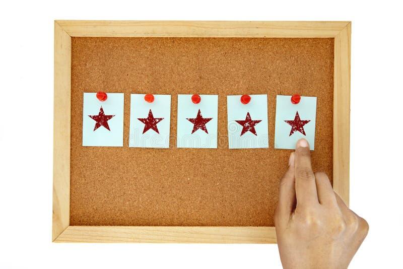 Perno della mano una carta per appunti sul bordo del perno del sughero con dare cinque stella, simbolo del concetto eccellente di immagini stock libere da diritti