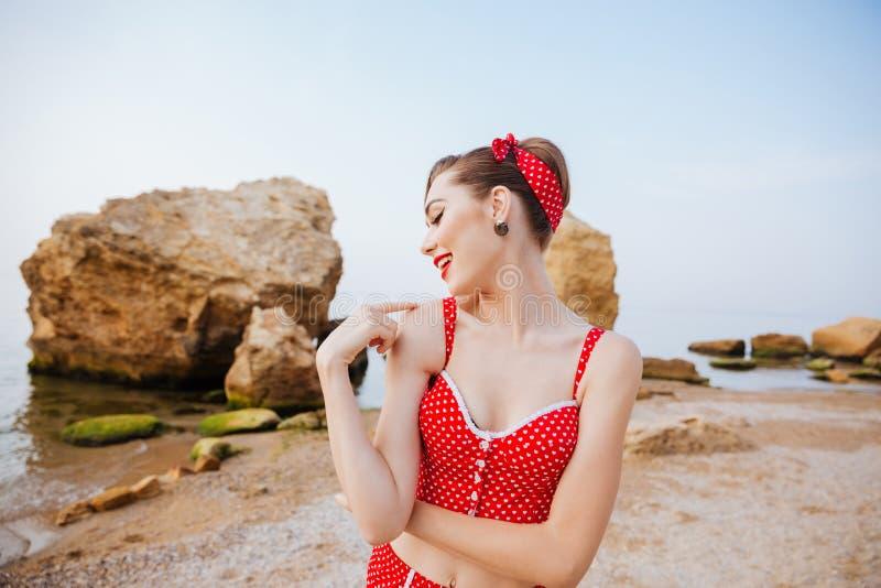 Perno hermoso joven encima de la muchacha en la presentación roja del traje de baño foto de archivo