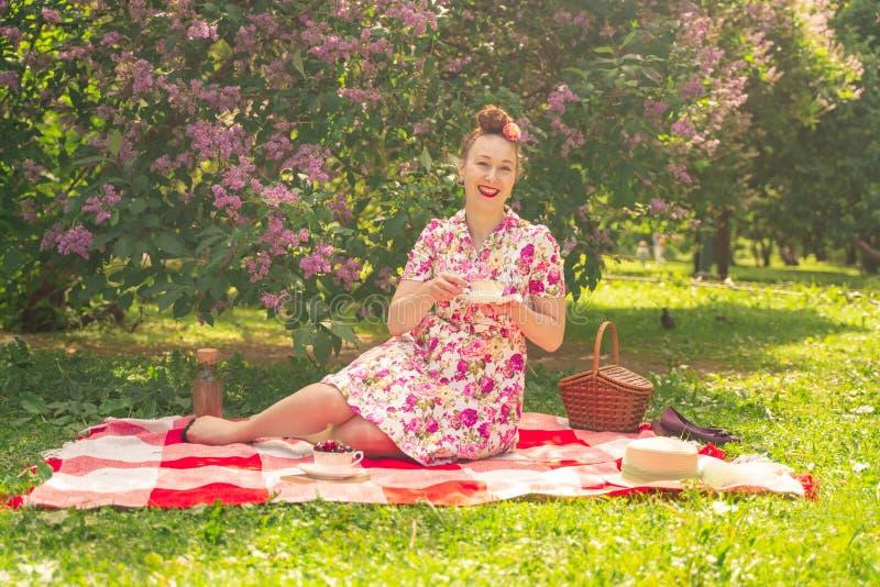 Perno joven bonito encima de la muchacha que tiene resto en la naturaleza vestido delgado feliz del vintage de la mujer que lleva fotografía de archivo