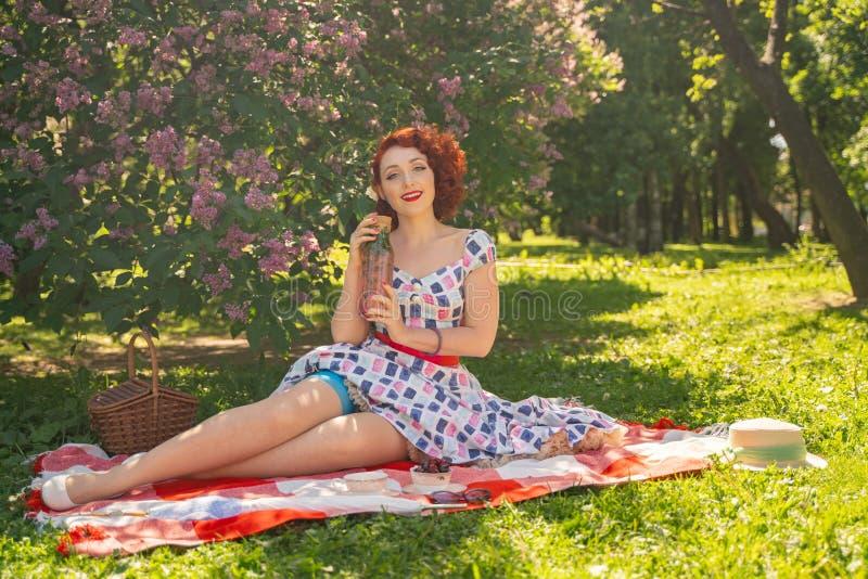 Perno joven bonito encima de la muchacha que tiene resto en la naturaleza vestido delgado feliz del vintage de la mujer que lleva foto de archivo libre de regalías