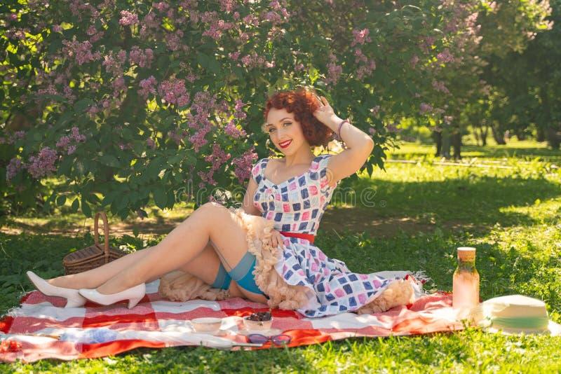 Perno joven bonito encima de la muchacha que tiene resto en la naturaleza vestido delgado feliz del vintage de la mujer que lleva imagenes de archivo
